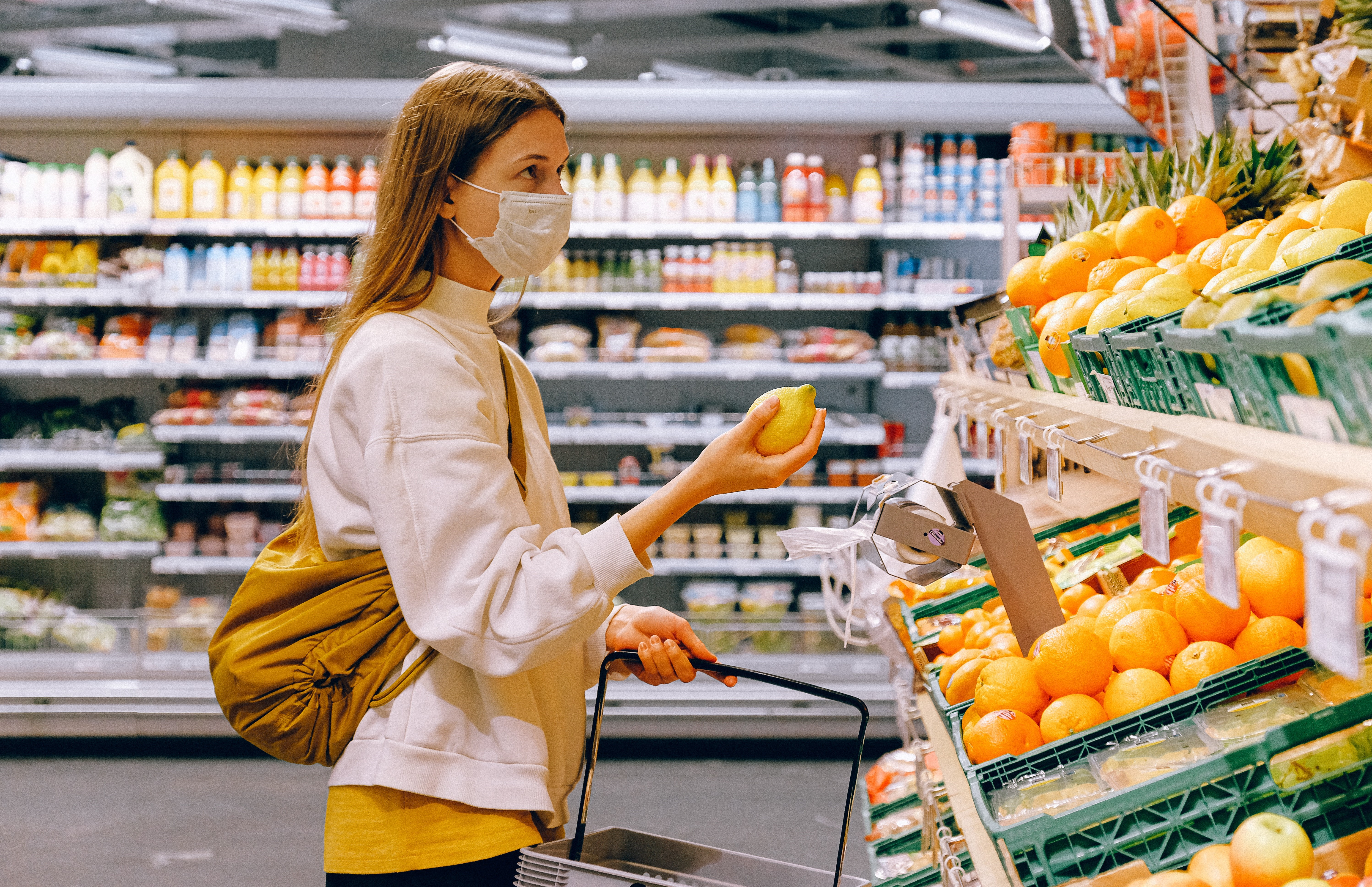 woman-in-yellow-tshirt-and-beige-jacket-holding-a-fruit